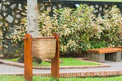 Wicker basket for garbage on a city street in Louangphabang, Laos. Copy space for text. Royalty Free Stock Image