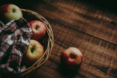 Wicker basket with the gifts of summer apples. Wicker basket with colorful apples covered with a cloth in a cage on a wooden rural background stock photo