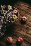 Wicker basket with the gifts of summer apples. Wicker basket with colorful apples covered with a cloth in a cage on a wooden rural background royalty free stock images