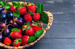 Wicker basket with grapes and strawberries Stock Photo