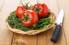 Wicker basket with greens and tomatoes and kitchen knife Royalty Free Stock Images