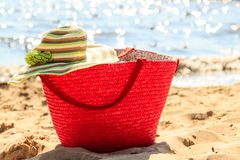 Wicker basket handbag bag and hat on summer beach. Stock Photography