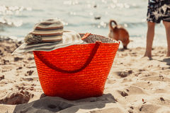 Wicker basket handbag bag and hat on summer beach. Royalty Free Stock Photography