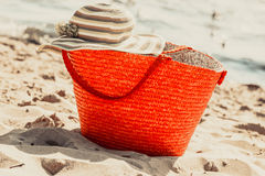 Wicker basket handbag bag and hat on summer beach. Royalty Free Stock Photo