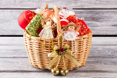 Wicker basket with handmade Christmas ornaments. Fairies, Christmas balls and bell in the basket. Preparation for Christmas Royalty Free Stock Image
