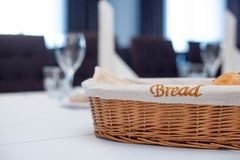 Wicker basket with the inscription bread on the table. With a white cloth against the background of the ceremonial hall royalty free stock photo