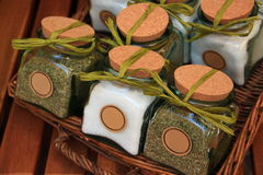 Wicker basket of jars with salt and spices. A wicker basket with jars containing salt and spices, closed with cork plugs and green ribbons stock images