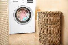 Wicker basket with laundry near washing machine. In bathroom stock image