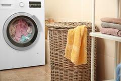 Wicker basket with laundry near washing machine Stock Photography