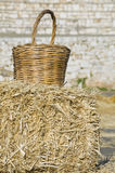 Wicker basket leaning on haystack bale. Stock Photography