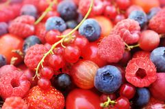 Wicker basket of mixed fresh ripe sweet berries royalty free stock images