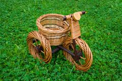 Wicker basket in motorcycle shape. On fresh green grass Royalty Free Stock Images