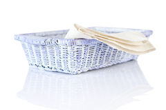 Wicker basket and napkin on white Stock Photos