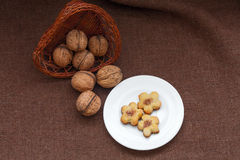 Wicker basket with nuts and pastry on a plate Royalty Free Stock Photos