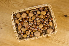 Wicker basket of nuts in straw Stock Photos