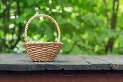 Wicker basket on old wooden table Royalty Free Stock Image