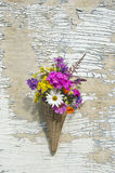 Wicker basket on old wooden wall with flowers Royalty Free Stock Photos