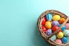Wicker basket with painted Easter eggs on color background, top view. Space for text royalty free stock photo