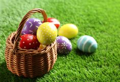 Wicker basket with painted Easter eggs on green grass. Space for text royalty free stock images