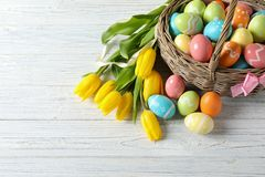 Wicker basket with painted Easter eggs and spring flowers on wooden background. Above view stock images