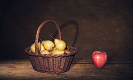 Wicker Basket with pears and one apple on table, dark painting background. Stock Photography