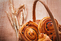 Wicker basket with raisin buns wheat ears on oaken. Wooden board food and drink concept Stock Photography