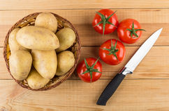 Wicker basket with raw potatoes, red tomatoes and kitchen knife Stock Images
