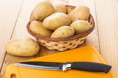 Wicker basket with raw washed potatoes, cutting board and knife Stock Photography