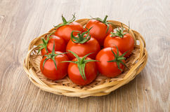 Wicker basket with red tomatoes on table Royalty Free Stock Images