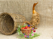 wicker basket with ripe berries and a wooden goose Royalty Free Stock Photo