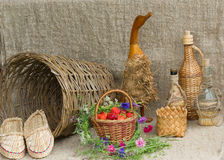 wicker basket with ripe berries ,a wooden goose and other utensils Royalty Free Stock Photo