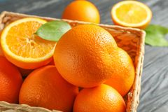 Wicker basket with ripe oranges on wooden table. Closeup stock photos