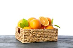 Wicker basket with ripe oranges on wooden table isolated on white background. Citrus food stock images