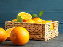 Wicker basket with ripe oranges on wooden table. Space for text royalty free stock image