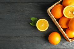 Wicker basket with ripe oranges on wooden table. Top view, space for text stock image