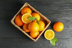 Wicker basket with ripe oranges on wooden table. Top view, space for text royalty free stock images