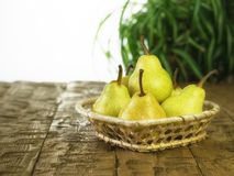Wicker basket with ripe pears on a wooden table. Ripe pears in a basket on a rustic wooden table. The concept of healthy eating with natural products Stock Photography