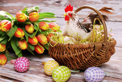 Wicker basket with rooster and eggs for easter Stock Photos