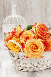 Wicker basket of roses on rustic wooden table. Royalty Free Stock Photo