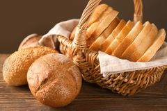 Wicker basket with sliced bread and fresh buns. On wooden table Royalty Free Stock Images