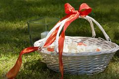 Wicker basket with some flowers. Wicker white basket with a red ribbon and some petals inside it Stock Photo
