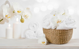Wicker basket with spa towels on table over abstract background Stock Photos