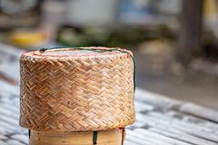 Wicker basket sticky rice on battens bamboo floor. Close up Thai sticky rice wicker basket on battens bamboo floor with blurry background royalty free stock photos