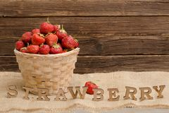 Wicker basket with strawberries on a tablecloth and strawberry inscription on a brown wooden background Royalty Free Stock Image