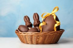 Wicker basket with sweet chocolate Easter eggs and bunnies on table. Against color background royalty free stock photography