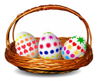 Wicker basket with three painted Easter eggs Royalty Free Stock Photography
