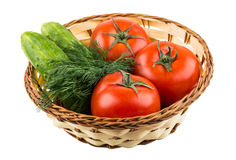 Wicker basket with tomatoes, cucumbers and dill Stock Photos