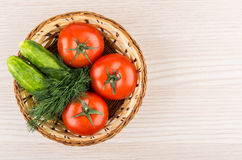 Wicker basket with tomatoes, cucumbers and dill on wooden table Stock Images
