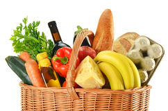 Wicker basket with variety of grocery products on white Royalty Free Stock Photography