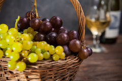 Wicker basket with various grapes: red, white and black berries on the dark wooden table with bottle and glass of white wine in th. E background.. Selective Stock Image